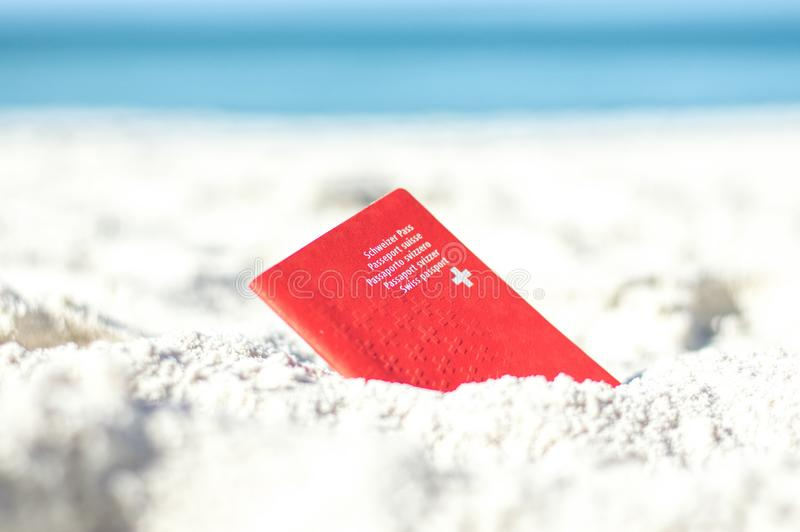 Passeport suisse dans le sable à la plage photographie stock