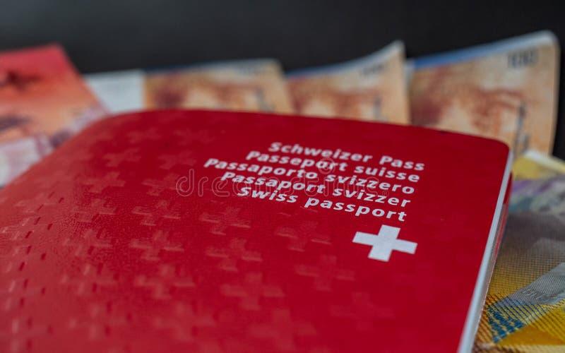 Passeport suisse et argent étroits sur la citoyenneté noire de la Suisse de fond photo libre de droits