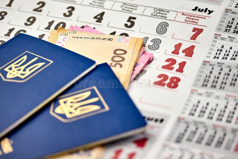 passeports avec la fin de monnaie fiduciaire de devise nationale vers le haut de la vue de l'argent liquide sur un fond de calend photos stock