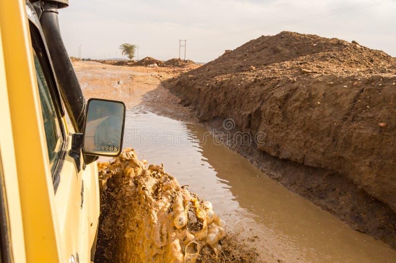Passera till och med gyttjan med en jeep på spåret i klyfta för Kenya ` s royaltyfri bild
