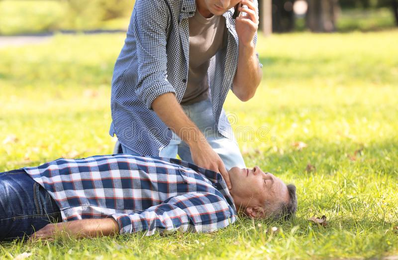 Passerby calling ambulance while checking pulse of unconscious man outdoors. Passerby calling ambulance while checking pulse of unconscious men outdoors. First royalty free stock photo