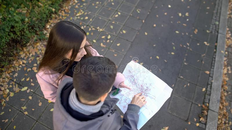 Passerby helping male tourist search destination place on city map, sightseeing. Stock photo stock photo