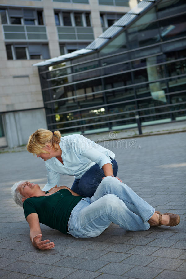 Passerby helping senior woman. Passerby helping a senior women with seizure royalty free stock photos
