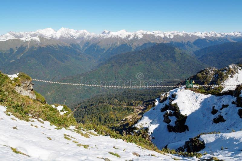 Passerella della sospensione nelle alte montagne nevose fotografia stock