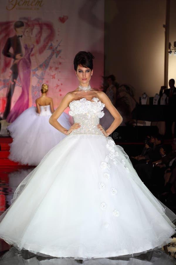 Passerella di modello delle camminate del vestito da cerimonia nuziale di usura immagini stock libere da diritti