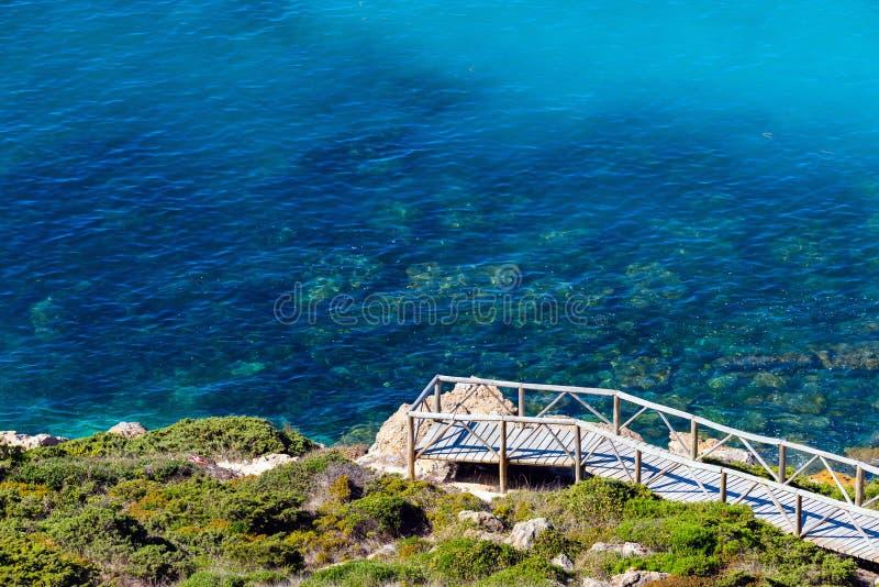 Passerelle en bois sur la côte le long de la mer avec de l'eau transparent clair photo libre de droits