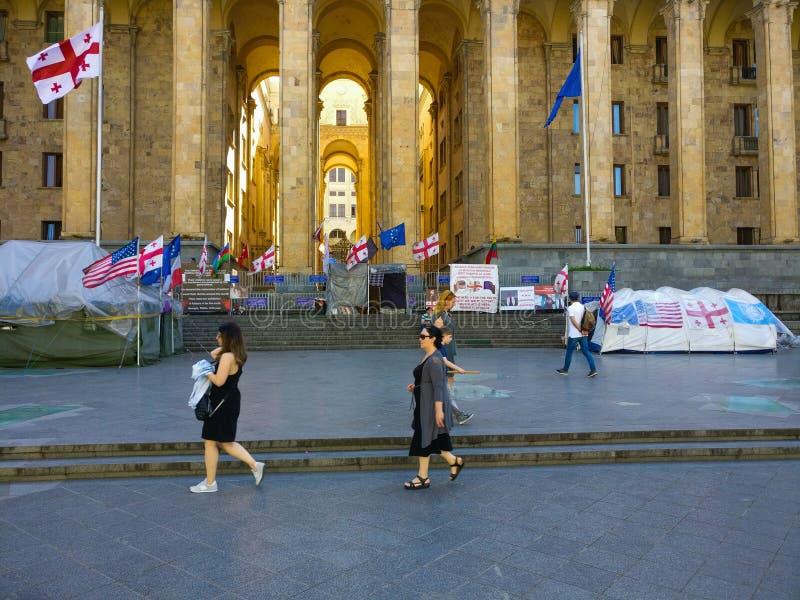 Passers by walk através do parlamento georgiano na cidade de Tbilisi, Geórgia imagem de stock