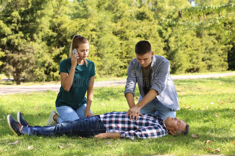 Passersby helping unconscious man outdoors royalty free stock images