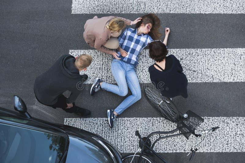 Passersby som hjälper olycksoffret av en bilolycka arkivbilder