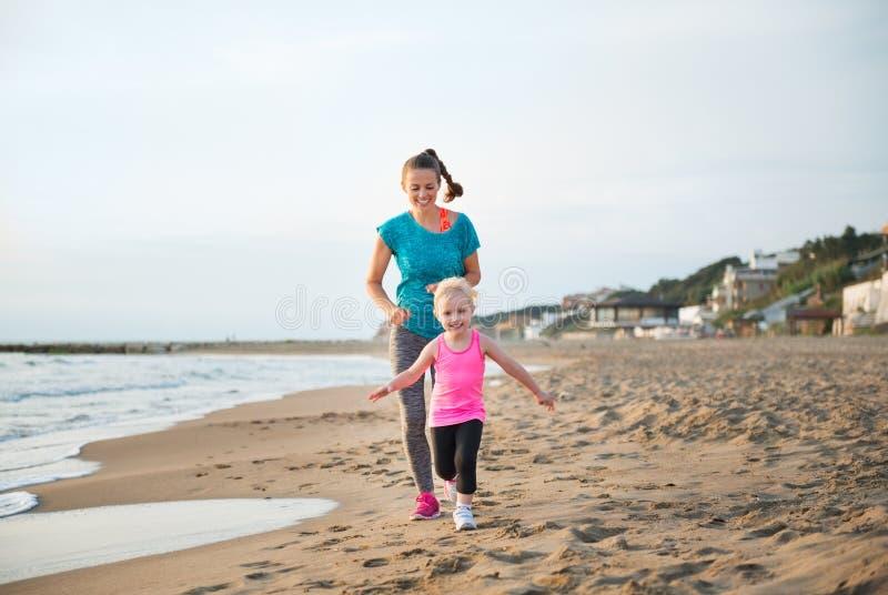 Passform lycklig moderspring bak ung dotter på stranden royaltyfri bild