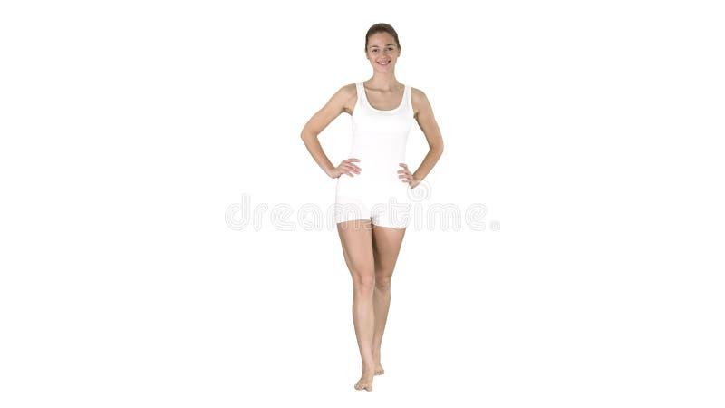 Passform och sportig flicka i den vita underkläderna som barfota går med händer på hennes höfter på vit bakgrund arkivbilder