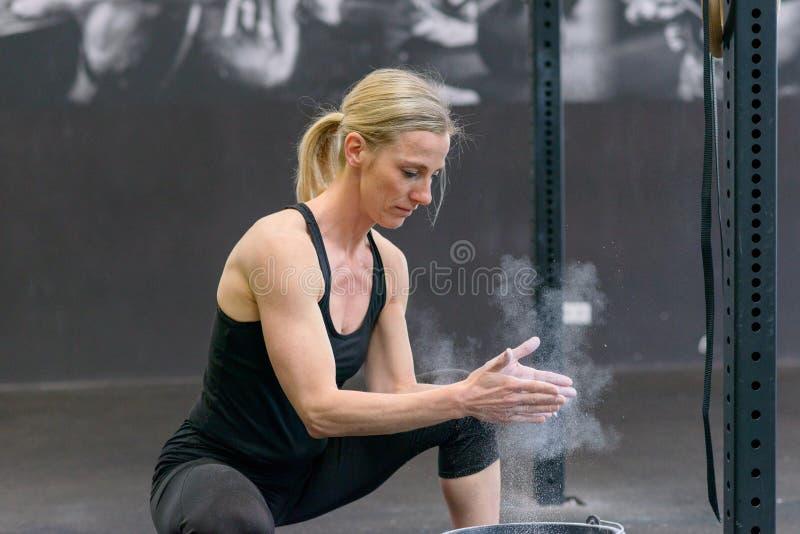 Passform tonad blond kvinna som applicerar krita till henne händer fotografering för bildbyråer