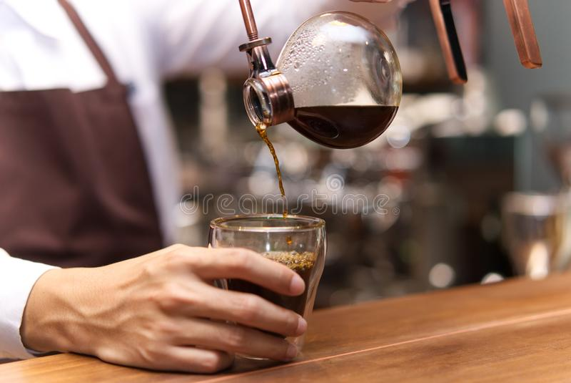 Passi il caffè del sifone del gocciolamento, barista che versa il caffè preparato nel Cu fotografia stock