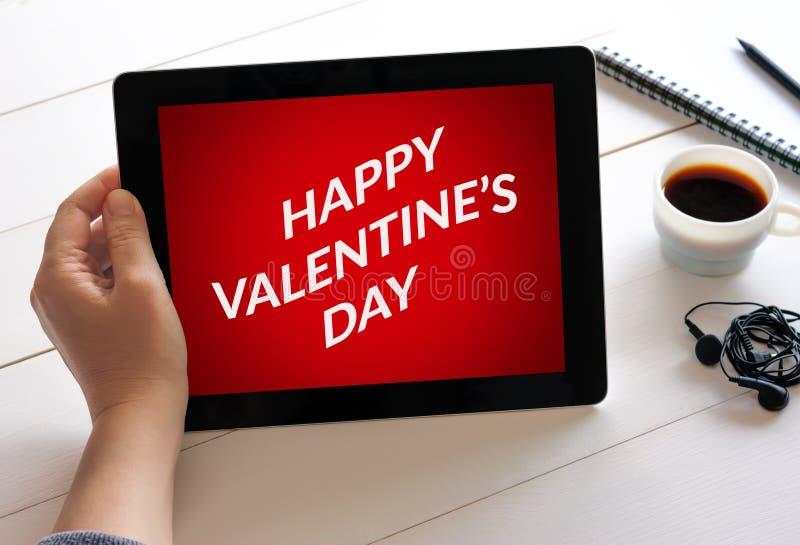 Passi il computer della compressa della tenuta con il concetto del giorno del ` s del biglietto di S. Valentino sull'SCR fotografie stock libere da diritti