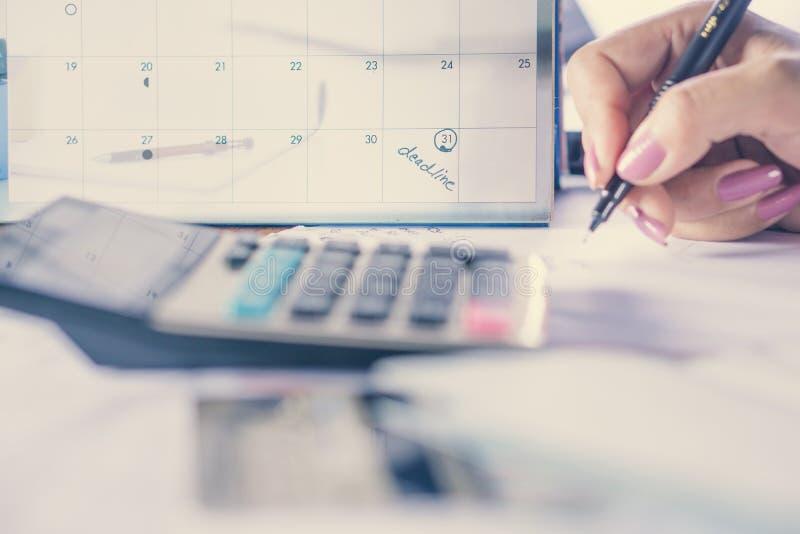 Passi il fuoco calcolatore di concetto di pagamento e di debito sulla nota del calendario di termine fotografie stock