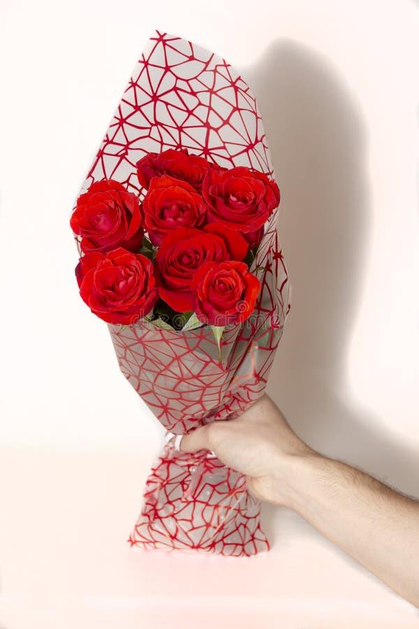 Passi il mazzo della tenuta delle rose rosse sopra fondo bianco fotografie stock