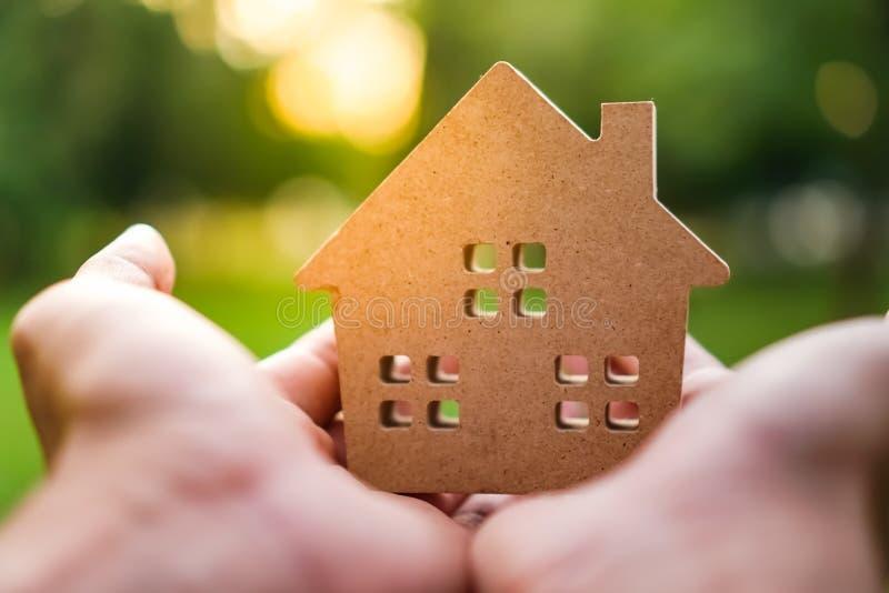 Passi il modello della casa della tenuta sul fondo verde della natura immagini stock libere da diritti