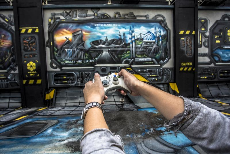 Passi il regolatore di gioco della tenuta redatto nel fondo di gioco nel grey, in blu ed in arancia fotografia stock