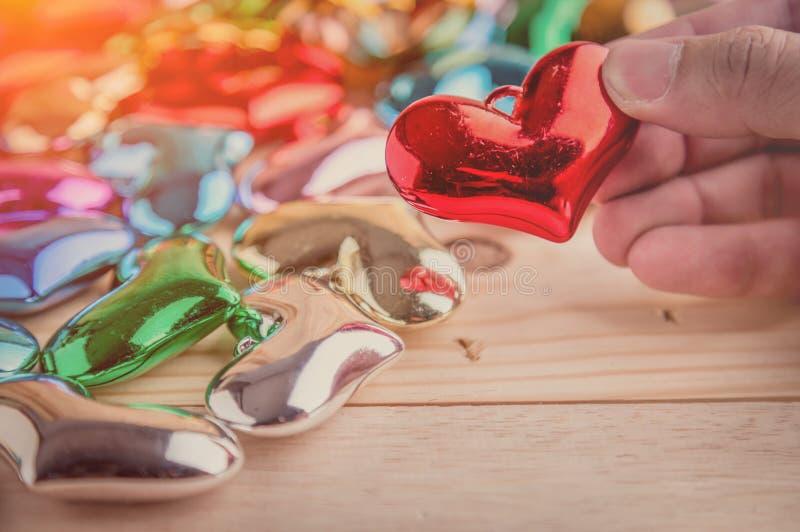 Passi il selezionamento degli oggetti brillanti rossi del cuore dagli altri cuori fotografia stock libera da diritti