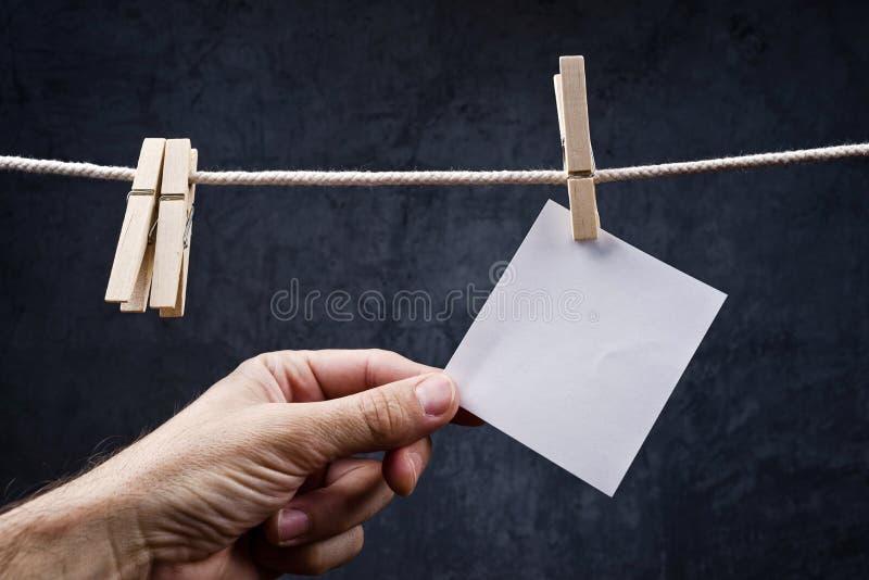 Passi il selezionamento della carta per appunti in bianco allegata alla corda con le mollette per il bucato immagine stock libera da diritti