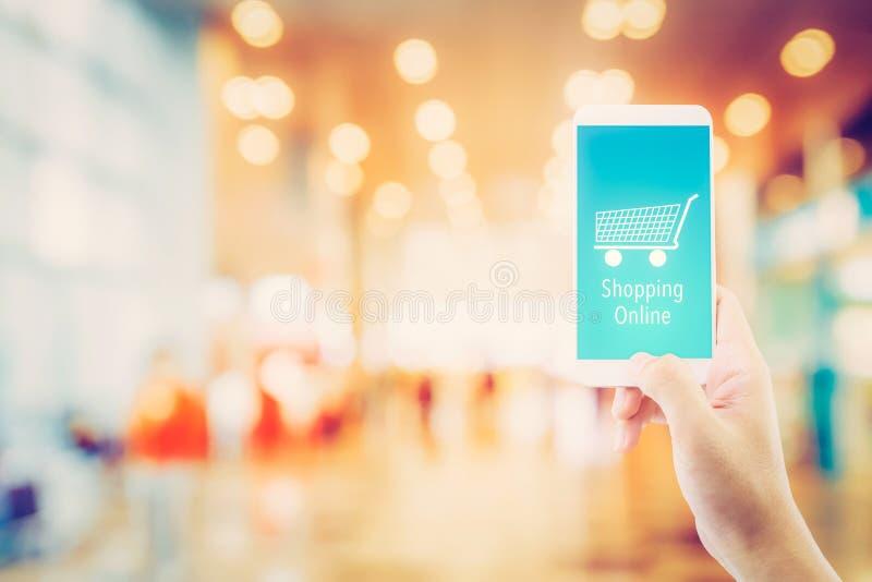 Passi il telefono cellulare della tenuta con la compera online sullo schermo fotografie stock