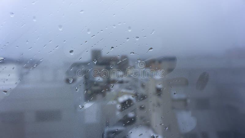 Passi il tiraggio e le gocce dell'acqua sul vetro di finestra fotografia stock
