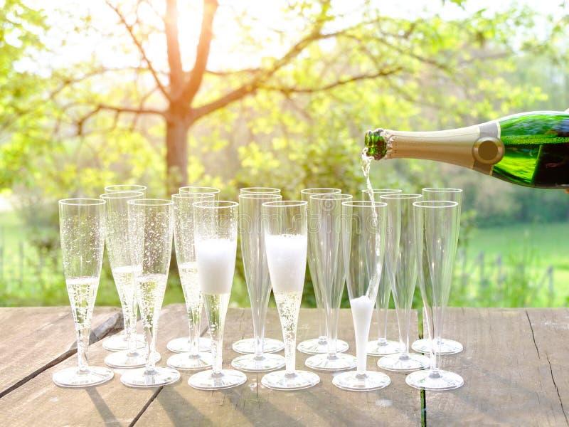 Passi il vino di versamento nei vetri di flauto di champagne immagini stock libere da diritti
