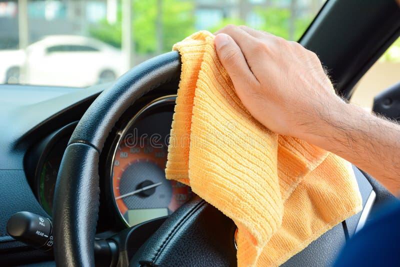 Passi il volante dell'automobile di pulizia con il panno del microfiber fotografia stock libera da diritti