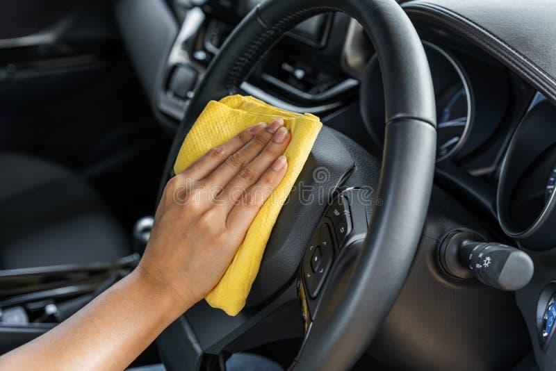 Passi il volante di pulizia dell'automobile con il panno del microfiber fotografia stock