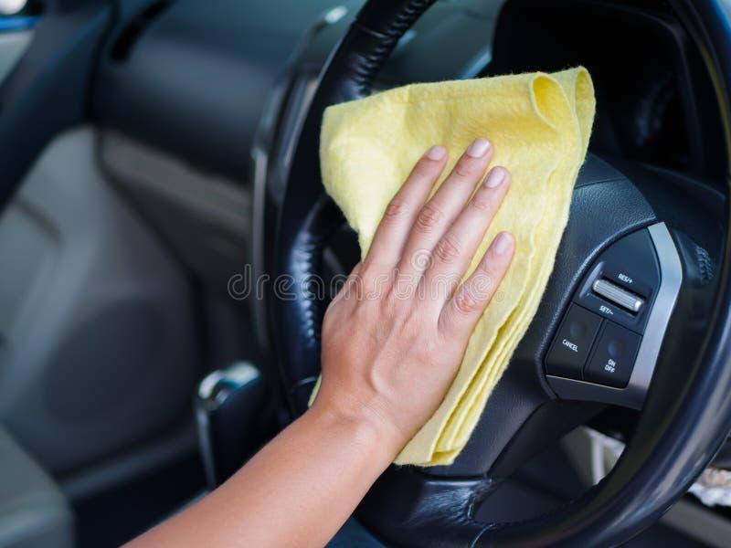Passi il volante interno di pulizia dell'automobile con il panno del microfiber immagine stock