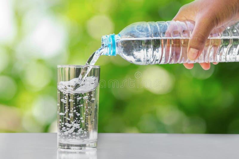 passi l'acqua potabile di versamento nella bottiglia di vetro della forma sulla tavola con immagine stock libera da diritti