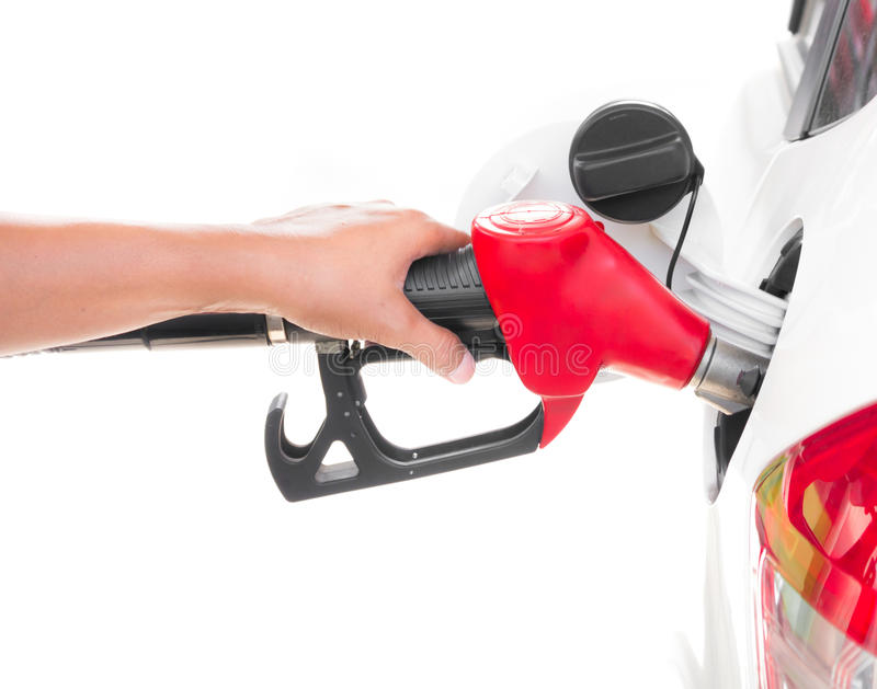 Passi l'ugello della benzina della tenuta che riempie un'automobile isolata su bianco fotografia stock