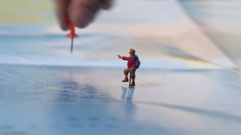 passi la collocazione del perno rosso con figura miniatura del viaggiatore la mini con immagine stock