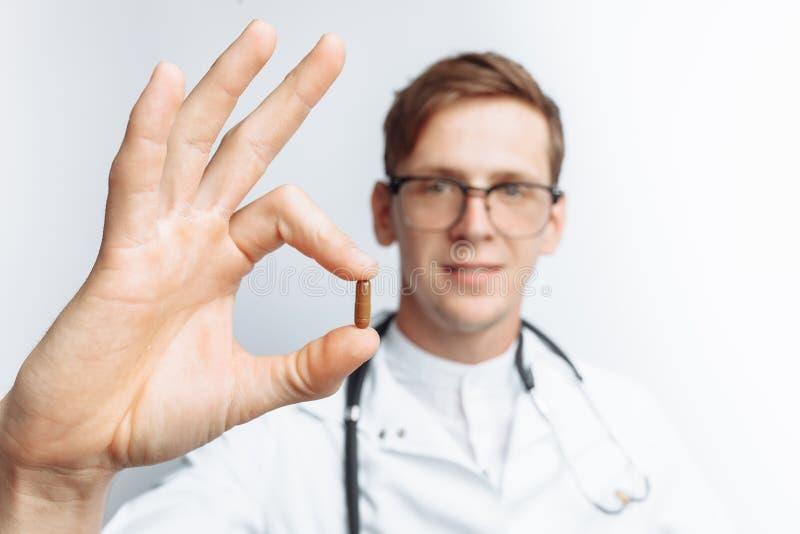 Passi la compressa della tenuta di medico, il primo piano, fondo bianco, per la pubblicità, inserzione del testo fotografia stock