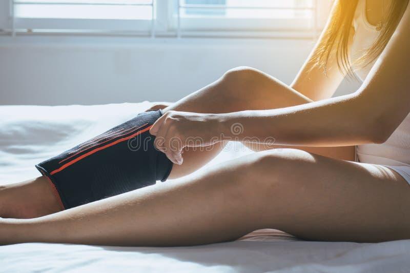 Passi la femmina che per mezzo della fasciatura elastica con la gamba, fasciatura mettente femminile sul suo ginocchio danneggiat fotografie stock libere da diritti
