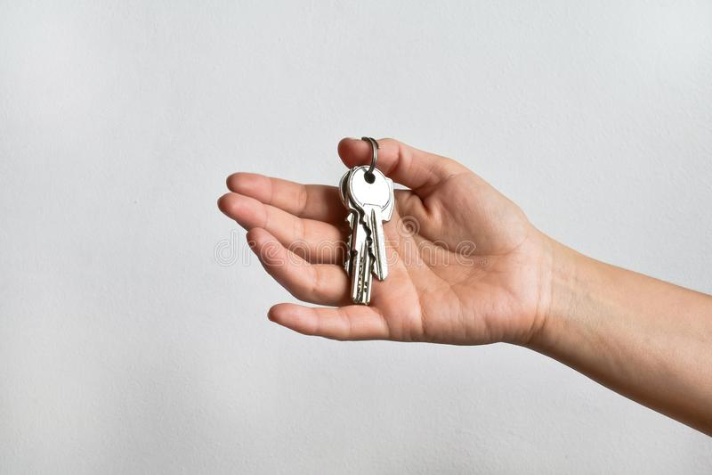 Passi la femmina con un mazzo di chiavi sul fondo di bianco della parete immagine stock