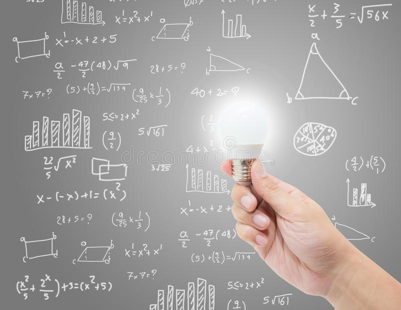 Passi la lampadina della tenuta con l'idea creativa di lampo di genio sul fondo di formula di per la matematica fotografie stock libere da diritti