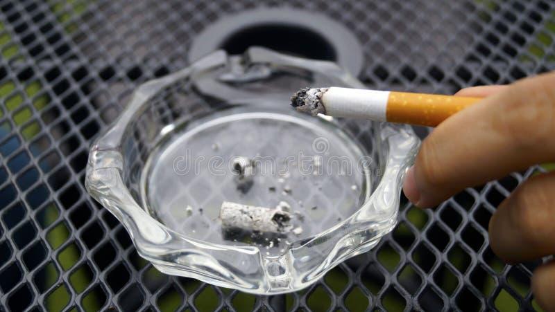 Passi la luce hilding su cigarrete sopra un vassoio di cenere fotografia stock