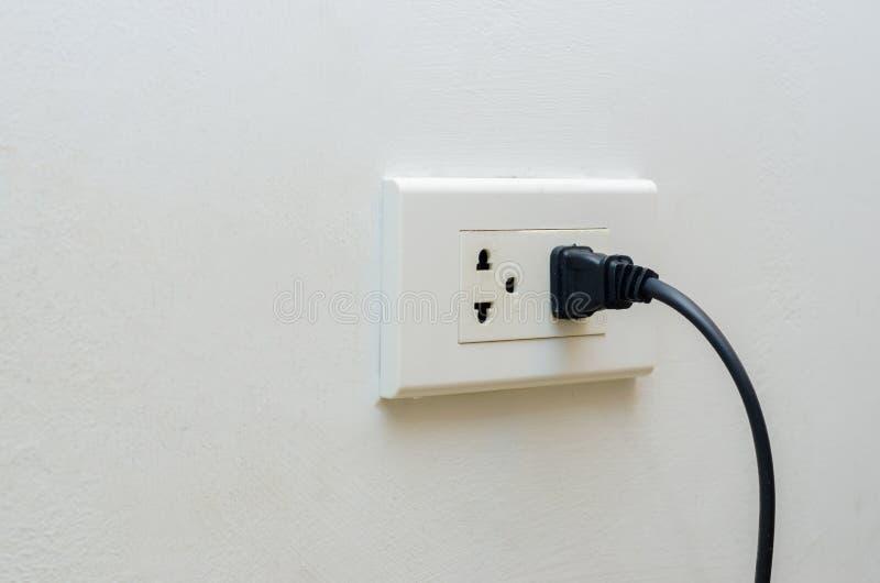Passi la mano del risparmio di energia dello sbocco che inserisce la spina elettrica nello sbocco fotografia stock libera da diritti