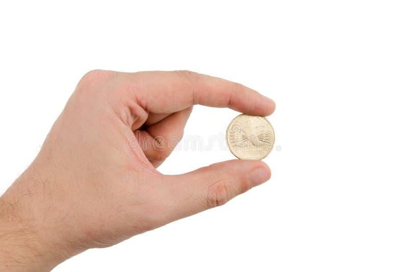 Passi la moneta del dollaro dell'oro della holding fotografia stock