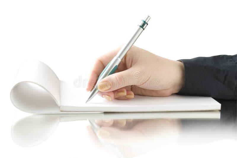 Passi la penna e la scrittura di conservazione sul taccuino immagine stock libera da diritti
