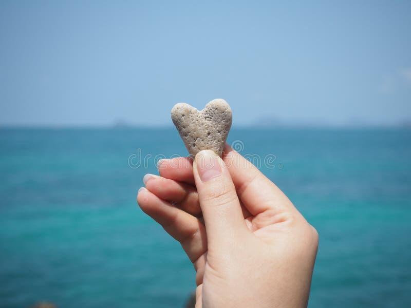 Passi la pietra di forma del cuore della tenuta sopra il fondo della spiaggia dell'estate fotografie stock libere da diritti