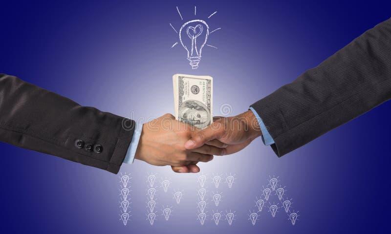 Passi la scossa fra un uomo d'affari con i soldi del dollaro per l'idea della s fotografia stock libera da diritti