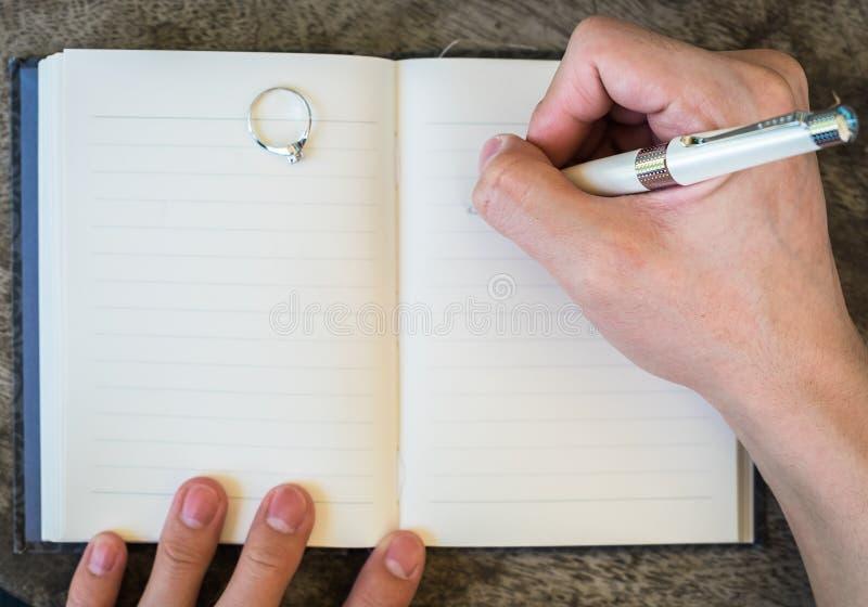 Passi la scrittura del taccuino bianco della penna con l'anello di diamante immagini stock libere da diritti