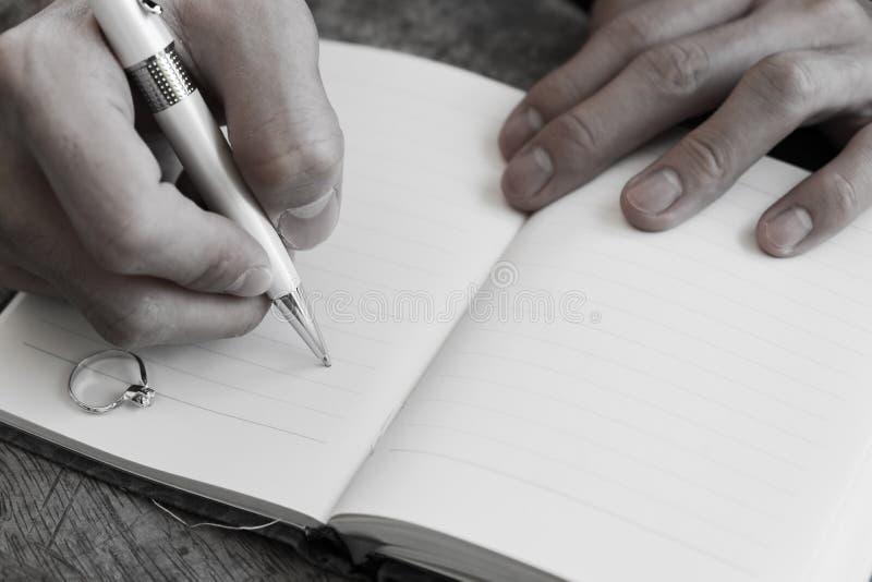 Passi la scrittura del taccuino bianco della penna con l'anello di diamante fotografia stock libera da diritti