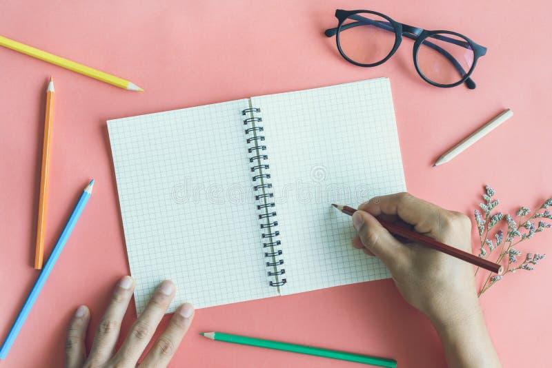 Passi la scrittura sul taccuino in bianco con le matite di colore sul backg di colore fotografia stock
