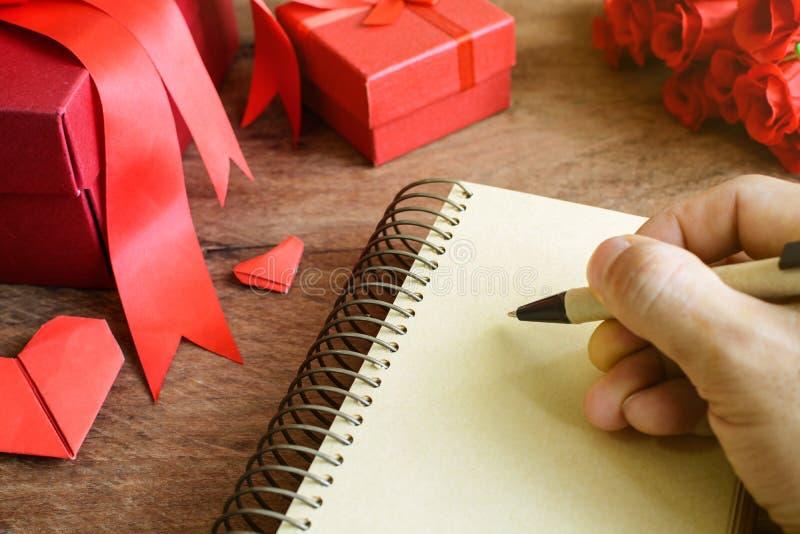 Passi la scrittura sul taccuino con il contenitore ed il fiore di regalo rossi su di legno immagine stock