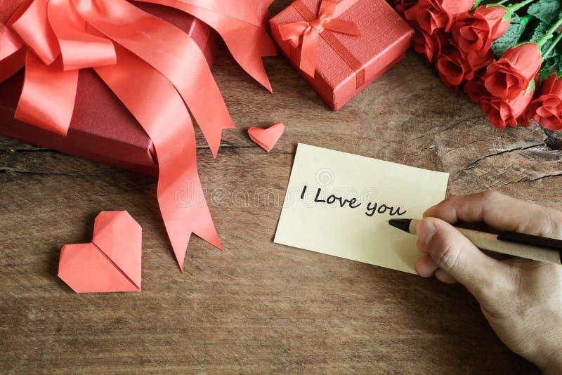 Passi la scrittura sul taccuino con il contenitore ed il fiore di regalo rossi su di legno fotografia stock