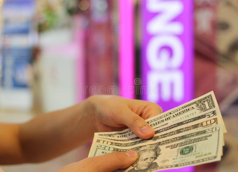 Passi la tenuta dei soldi del dollaro americano per lo scambio ed offuschi il fondo fotografia stock
