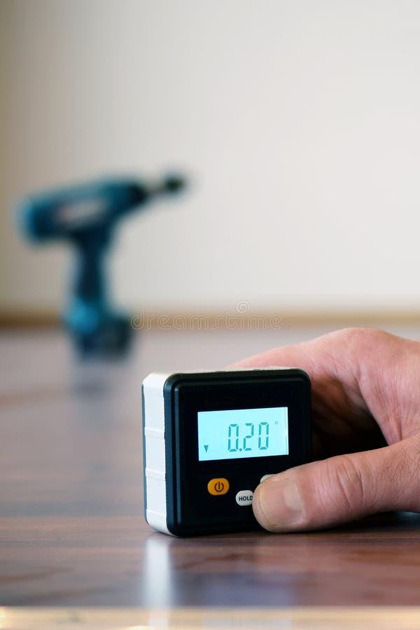 Passi la tenuta del livello di spirito digitale piccolo sul pavimento di parquet fotografia stock